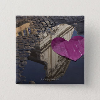 Lonely paper heart floating in a puddle. pinback button
