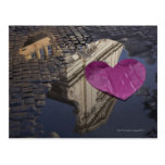 Lonely paper heart floating in a puddle. postcard