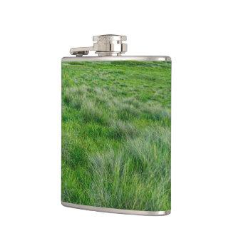 Long grasses in a vast grassland hip flasks