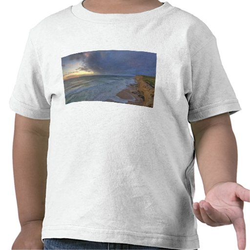 Los acantilados del mar cogen la luz pasada de los camiseta