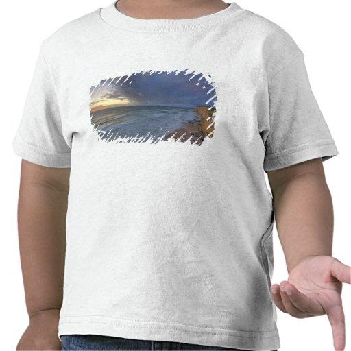 Los acantilados del mar cogen la luz pasada de los camisetas
