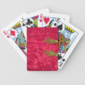 Los brazos de la mujer en piscina baraja cartas de poker