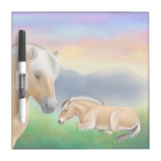 Los caballos noruegos del fiordo en descanso secan tableros blancos