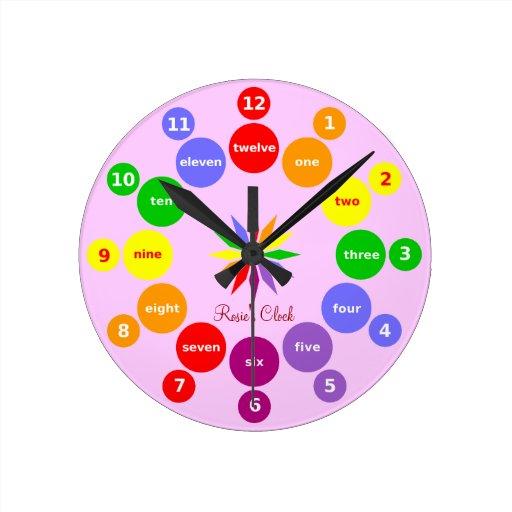 Los chicas aprenden números en reloj de pared rosa