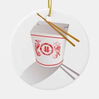 Los chinos sacan la caja de la comida con los adorno navideño redondo de cerámica