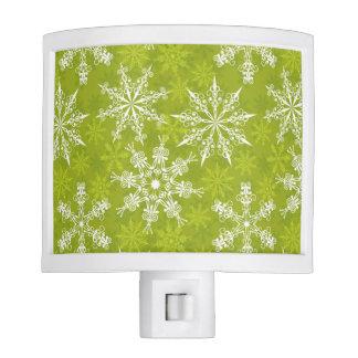 Los copos de nieve modelan en verde luces de noche