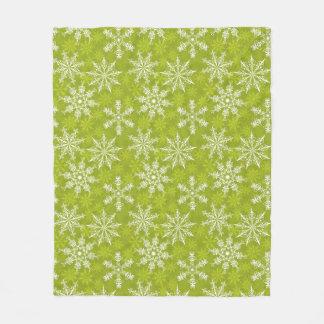Los copos de nieve modelan en verde manta de forro polar