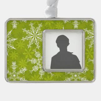 Los copos de nieve modelan en verde marcos de adorno plateado