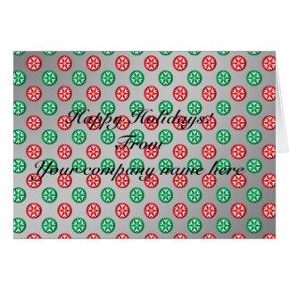 Los copos de nieve verdes rojos en círculos en la  tarjeta de felicitación