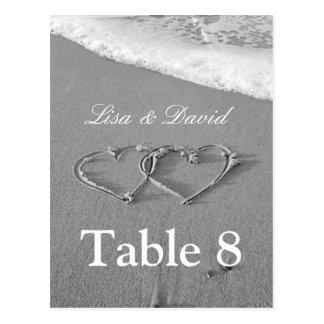 Los corazones en tabla de la arena numeran tema de postal