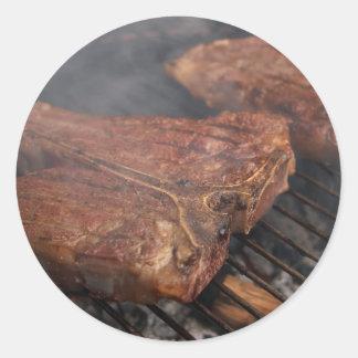 Los filetes que asan a la parrilla la barbacoa pegatina redonda