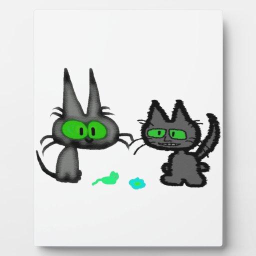 Los gatos de ojos verdes con allí juegan placas