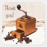 Los granos de café y el molino de café viejo le pegatina cuadrada