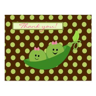 Los guisantes de los gemelos del chica en una fies tarjeta postal