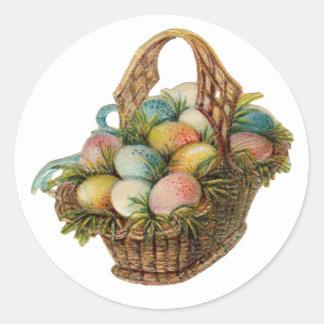 Los huevos de Pascua coloridos llenan una cesta de Etiquetas Redondas