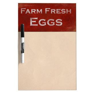 Los huevos frescos de la granja secan al tablero d pizarras