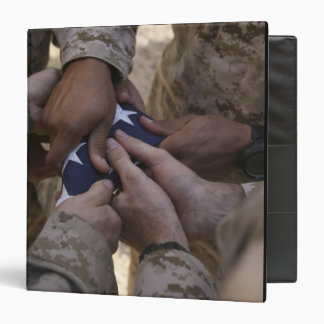 Los infantes de marina doblan una bandera american