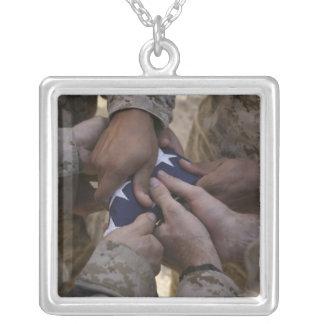 Los infantes de marina doblan una bandera american grimpola
