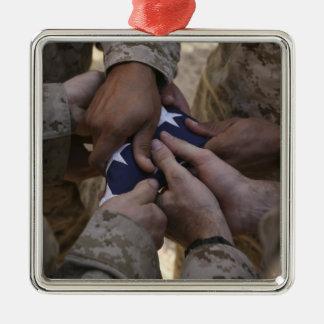 Los infantes de marina doblan una bandera american adornos