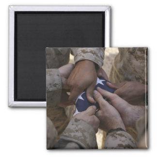 Los infantes de marina doblan una bandera american imán de frigorifico