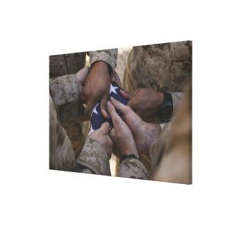 Los infantes de marina doblan una bandera american impresiones de lienzo