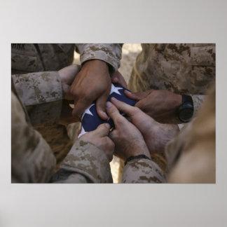 Los infantes de marina doblan una bandera american impresiones