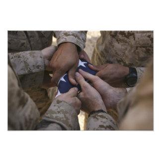 Los infantes de marina doblan una bandera american fotografías
