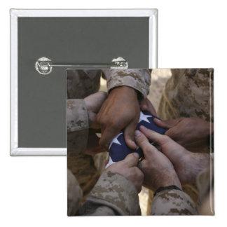 Los infantes de marina doblan una bandera american pin