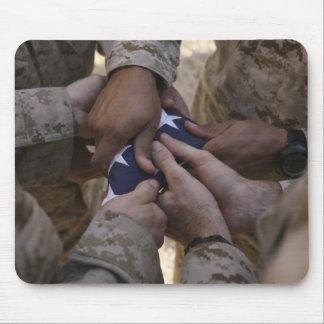 Los infantes de marina doblan una bandera american alfombrilla de ratón