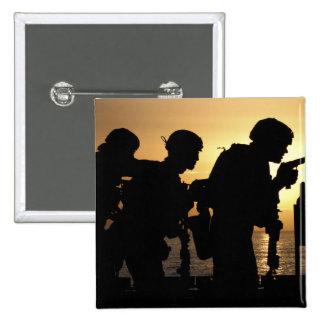 Los infantes de marina encienden las armas de mano pin cuadrado