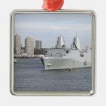 Los infantes de marina y los marineros sirven los adorno navideño cuadrado de metal