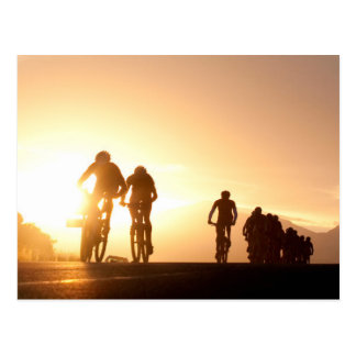 Los jinetes de la bici de montaña hacen su manera postal