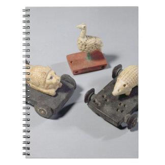 Los juguetes de los niños: un erizo, un león y una libros de apuntes con espiral