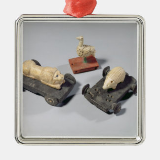 Los juguetes de los niños: un erizo, un león y una adorno cuadrado plateado