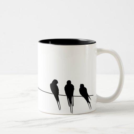 Los mirlos siluetean en el alambre taza