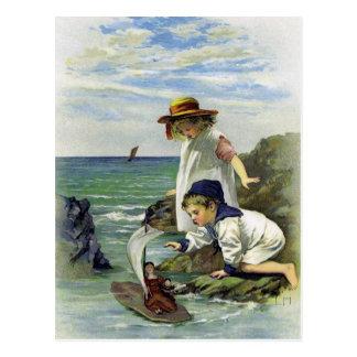 Los niños del vintage pusieron la muñeca al mar postal