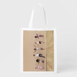 Los niños que saltan jugar dentro del ejemplo de bolsa para la compra