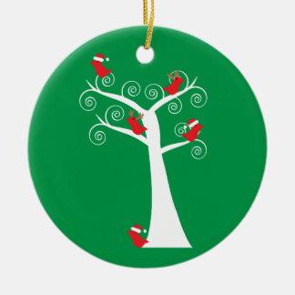 Los pájaros del navidad en un árbol personalizan adorno navideño redondo de cerámica