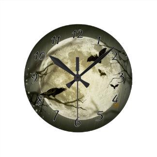 Los palos vuelan el cuervo se sientan delante de reloj redondo mediano