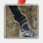 Los penachos del polvo descargan la costa de la adorno navideño cuadrado de metal