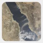 Los penachos del polvo descargan la costa de la pegatina cuadrada