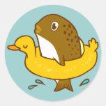 Los pescados en el anillo de la natación del pato pegatina redonda