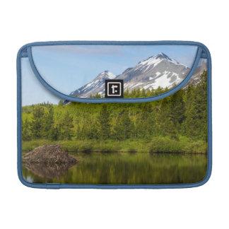 Los picos de montaña reflejan en una charca del funda macbook pro