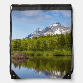 Los picos de montaña reflejan en una charca del mochila