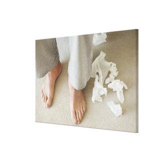 Los pies del hombre rodeados por los tejidos arrug lona envuelta para galerías