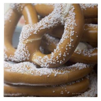 Los pretzeles enormes del vendedor ambulante de azulejo cuadrado grande