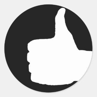 Los pulgares suben el gesto, negro detrás etiqueta redonda
