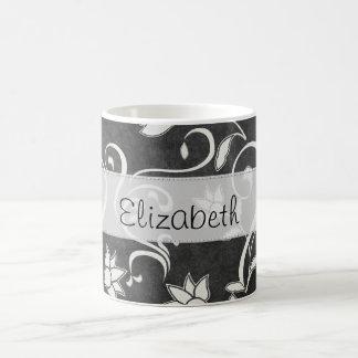 Los remolinos negros de la flor blanca cosieron la taza de café