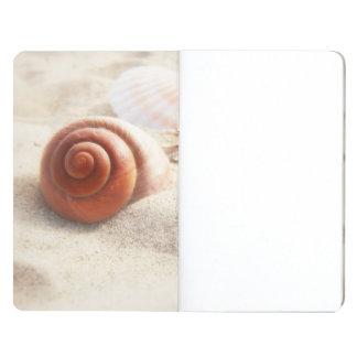 Los seashells en el cierre de la arena para arriba cuaderno