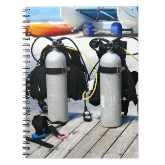 Los tanques de oxígeno para el buceo con libro de apuntes con espiral